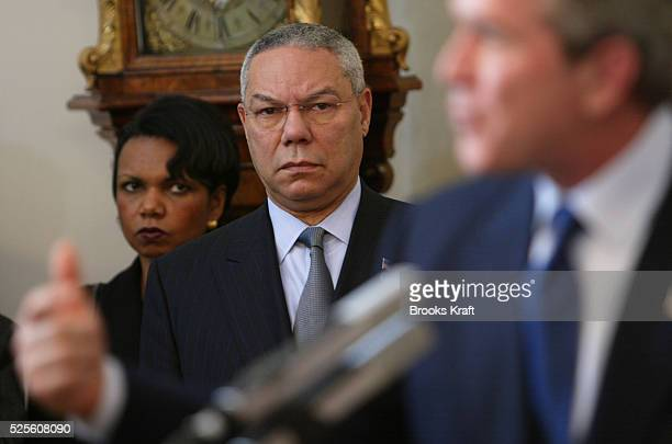 National Security Advisor Condoleezza Rice and Secretary of State Colin Powell watch as President George W Bush delivers a speech