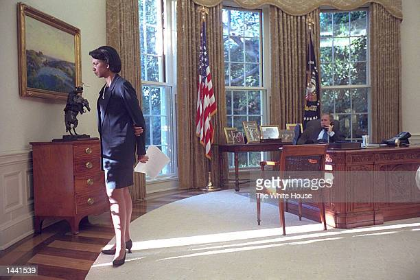 National Security Advisor Condoleezza Rice waits as US President George W Bush talks with British Prime Minister Tony Blair early September 12 2001...