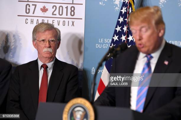 National Security Advisor John Bolton listens as US President Donald Trump speaks to reporters on June 9 during the G7 Summit in La Malbaie Quebec...
