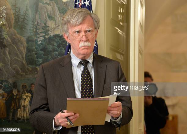 National Security Advisor John Bolton listens to remarks by US President Donald Trump as he speaks to the nation announcing military action against...