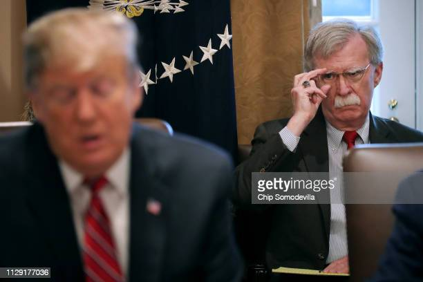 National Security Advisor John Bolton listens to US President Donald Trump talk to reporters during a meeting of his cabinet in the Cabinet Room at...