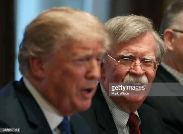 National Security Advisor John Bolton listens to US President Donald Trump as he speaks about the FBI raid at lawyer Michael Cohen's office while...