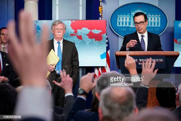 National Security Advisor John Bolton looks on as US Secretary of the Treasury Steven Mnuchin takes a question during a briefing in the Brady...