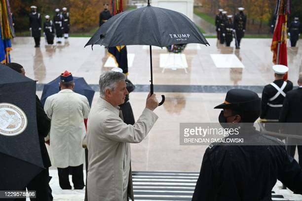 """National Security Advisor Robert OBrien holds an umbrella as US President Donald Trump attends a """"National Day of Observance"""" wreath laying ceremony..."""