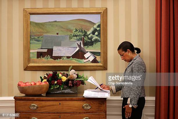 National Security Advisor Susan Rice looks over documents as President Barack Obama talks with reporters following a meeting with his national...