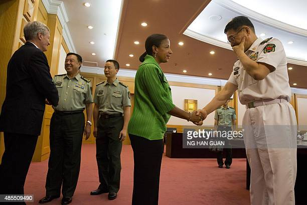 US National Security Advisor Susan Rice shakes hands with a Chinese military officer as Chinese Central Military Commission Vice Chairman Fan...