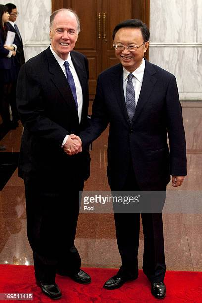 National Security Advisor Tom Donilon and Chinese State Councilor Yang Jiechi shake hands before their meeting at Diaoyutai State Guesthouse on May...