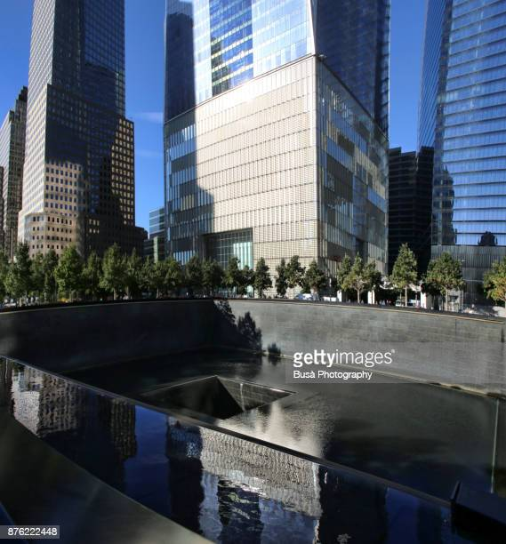 National September 11 Memorial at the World Trade Center site in Lower Manhattan, with the base of the Freedom Tower in the background. New York City, USA