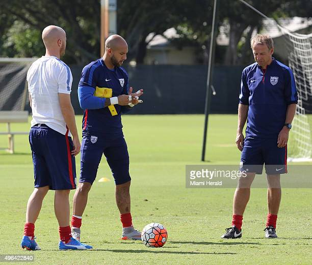 US National Soccer Team players Tim Howard center and Michael Bradley left talk to head coach Jurgen Klinsmann during training at Barry University on...
