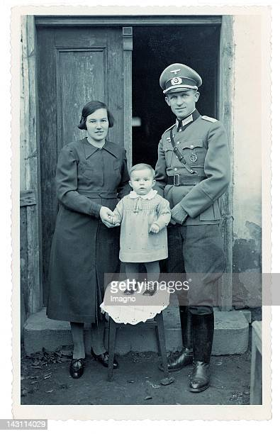 National Socialism. Officer of the Wehrmacht dressed in Uniform, his wife and his little child. Photograph. German. November the 12th, 1939.