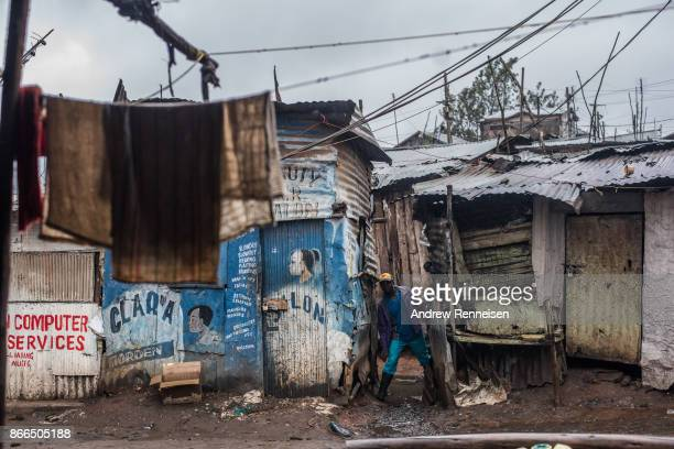 National Super Alliance protestor checks for nearby police officers in the Kibera slum on October 26 2017 in Nairobi Kenya Protestors boycotted the...