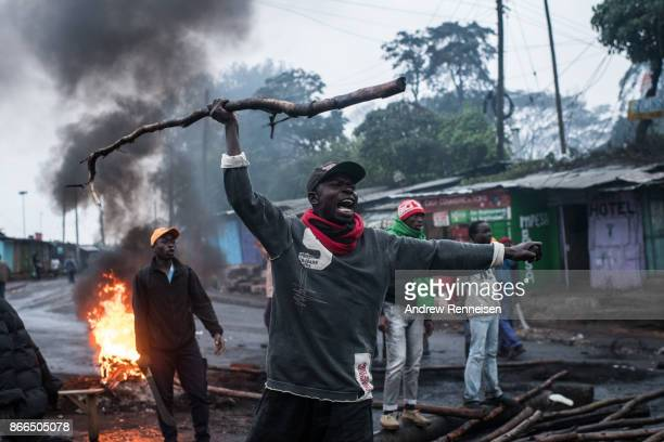 National Super Alliance protestor yells as nearby police officers approach in the Kibera slum on October 26 2017 in Nairobi Kenya Protestors...