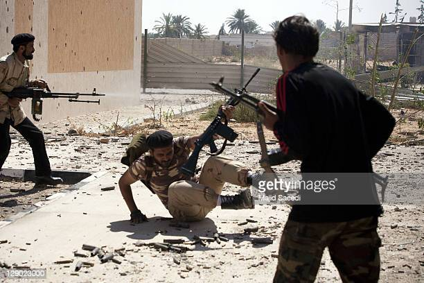 """National Transitional Council fighter falls while taking part in a street battle in the 700 complex area of """"Emarat"""" against Muammar Gaddafi's troops..."""