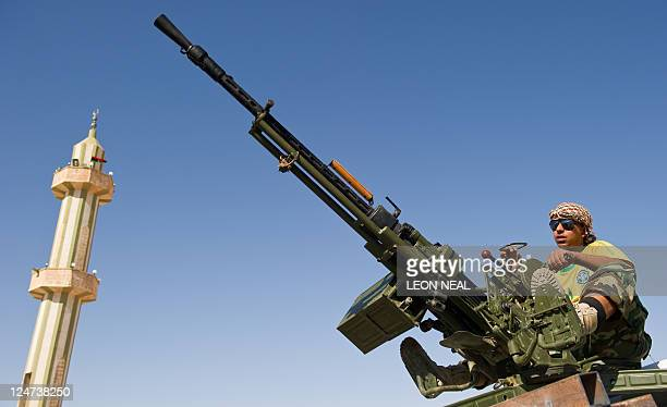 A National Transitional Council fighter sits on top of a truckmounted antiaircraft gun in Washtata on the road to Bani Walid on September 12 as...