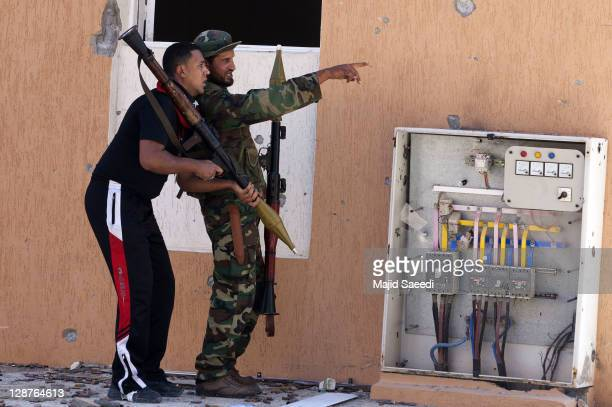 """National Transitional Council fighters look for targets during a battle in the 700 complex area of """"Emarat"""" against Muammar Gaddafi's troops on..."""