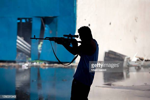 National Transitional Council fighters take part in a street battle in the center of the city on October 14, 2011 in Sirte, Libya. NTC fighters say...