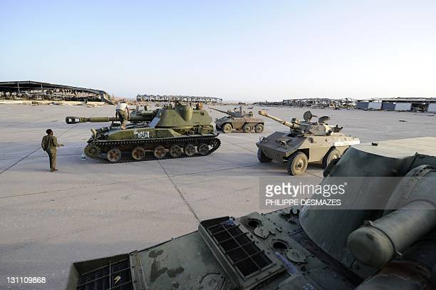 National Transitional Council forces remove tanks and APC's from the Drua military base hit by NATO bombing during it's offisive to help rebel...