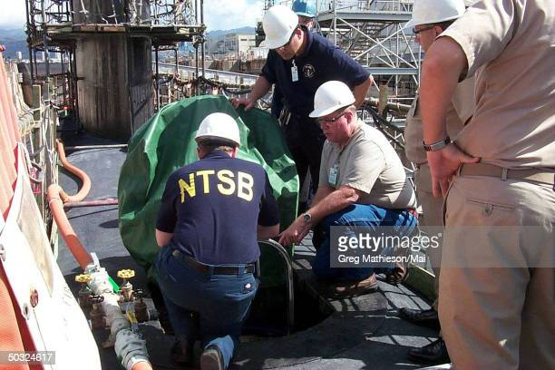 National Transportation Safety Board inspectors examining the escape trunk on USS Greenville while sub is dry docked at Pearl Harbor Naval Shipyard...