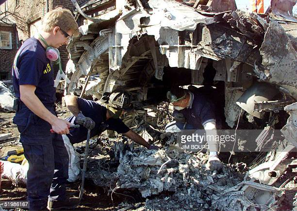 National Transportation Safety Board investigators search for evidence 14 November 2001 inside the destroyed tail section of American Airlines flight...