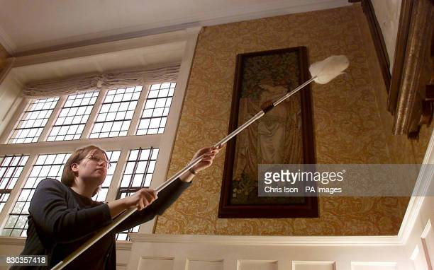 National Trust Conservation cleaner Emily Blanshard dusts a William Morris tapestry at Standen in Sussex All National Trust properties will open for...