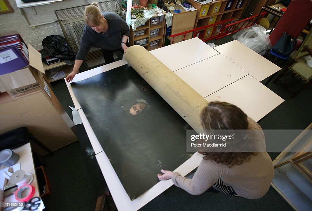 National Trust conservators unroll an 18th century painting rescued from Clandon Park House on April 30, 2015 near Guildford, England. The painting of Richard Onslow, Speaker of the House of Commons, was cut from it's frame by the fire brigade in order to remove it from the fire engulfing the house.