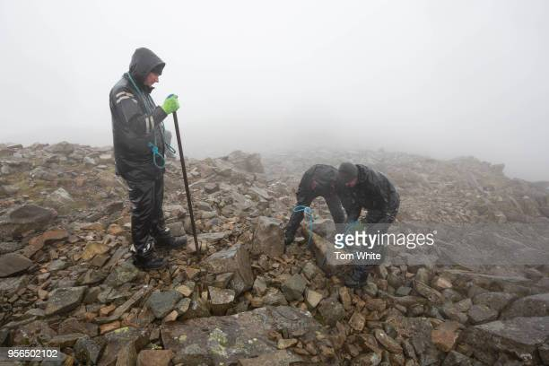 National Trust rangers haul huge rocks to help rebuild the summit cairn and World War 1 memorial at Scafell Pike on May 9 2018 in Seascale England...