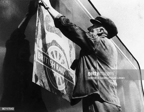 Nationalisation of the railway industry, 1948. A worker applies a transfer of the new British Railways logo to the side of a locomotive to mark the...