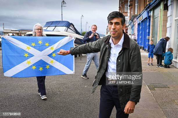 Nationalist demonstrators welcome Britain's Chancellor of the Exchequer Rishi Sunak as he visits Rothesay on the Isle of Bute, Scotland on August 07,...