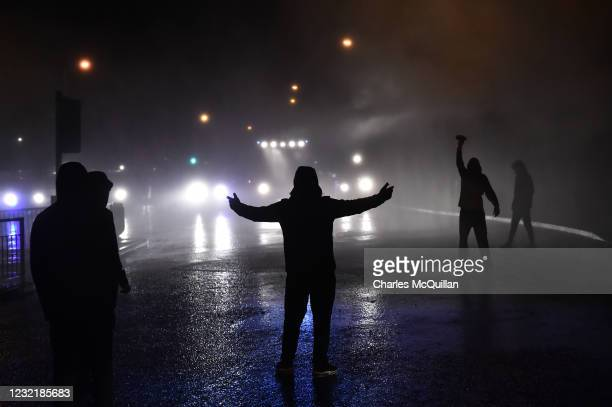 Nationalists approach police vehicles as they deploy water canons on Springfield Road just up from Peace Wall interface gates which divide the...