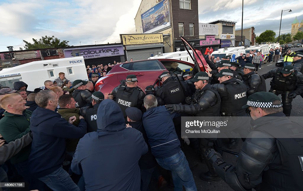 Nationalists join police officers to tip a car over in an attempt to free a young girl trapped underneath after an alleged loyalist drove over her as they reversed at high speed on the return journey towards the controversial Ardoyne flashpoint during the Twelfth of July parade on July 13, 2015 in Belfast, Northern Ireland. The Twelfth is an Ulster Protestant celebration held annually. It celebrates the victory of Protestant king William of Orange over Catholic king James II at the Battle of the Boyne in 1690, which helped ensure Protestant supremacy in Ireland at that time. This year the Twelfth takes place on the thirteenth of July due to the original date falling on a Sunday.