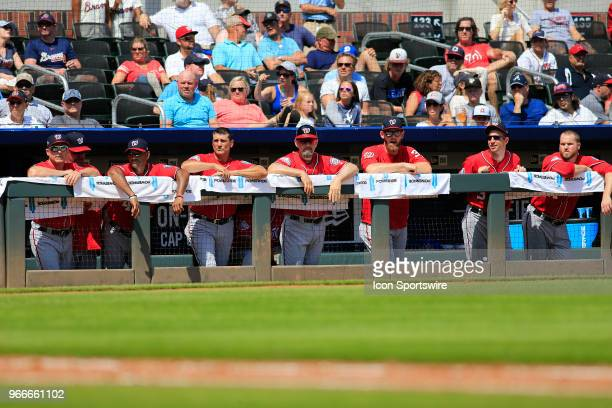 Nationals coaches and players lean on the dugout railing during the MLB game between the Washington Nationals and the Atlanta Braves on June 3 at...