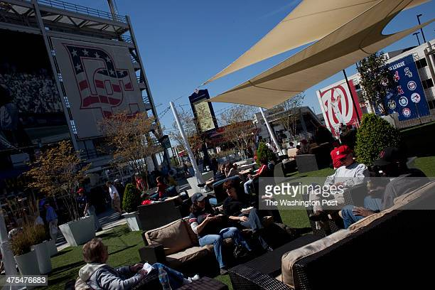 Nationals fans enjoy the April sunshine at the Miller Lite Scoreboard Walk at Nationals Park before the exhibition game against the Boston Red Sox on...