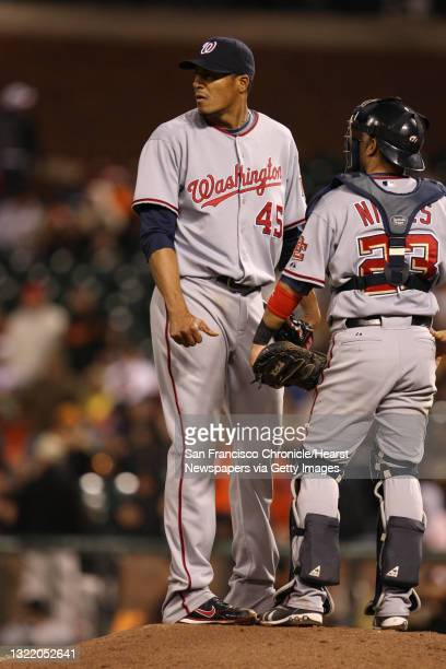 Nationals starting pitcher Daniel Cabrera talks with catcher Wil Nieves during their game against the Giants.