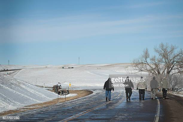 Native American activist walk down a road toward a contested bridge near Oceti Sakowin Camp on the edge of the Standing Rock Sioux Reservation on...