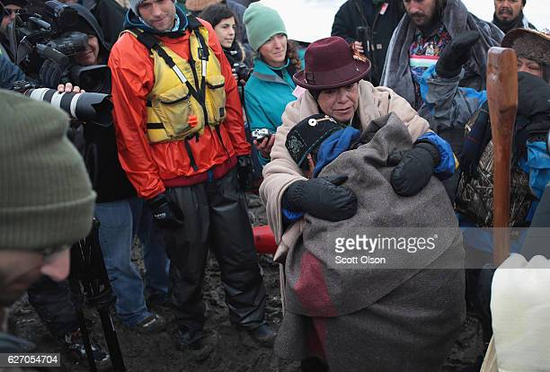 Native American activists from the Colville tribe in Washington state embrace after stepping on shore following a journey from the headwaters of the...
