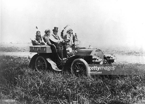 Native American Apache leader Geronimo wearing a top hat sits behind the wheel of a Locomobile Model C with Ponca leader Edward Le Clair Sr in the...