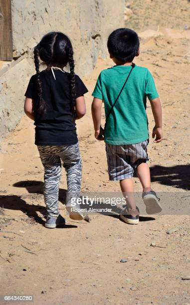 Native American boy and girl walk together at Sky City one of three Native American villages which make up Acoma Pueblo west of Albuquerque New...