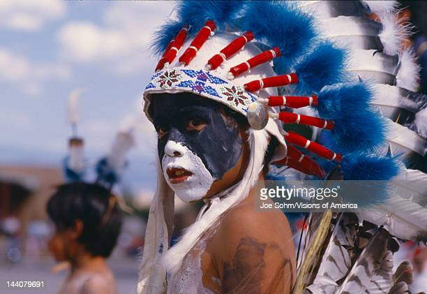 Native American boy with feathered headdress Corn Dance ceremony New Mexico