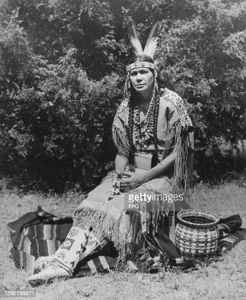 Native American Cherokee Princess Silver Heels, dressed in traditional fringed Cherokee clothing, with her hair in plaits, a feather headband, and...