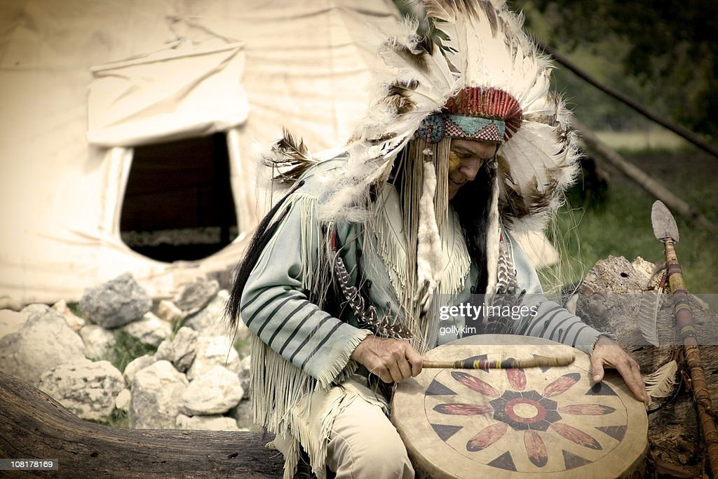 Native American Chief Playing Drum Outside Teepee : Stock Photo