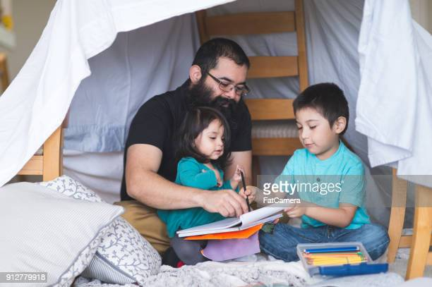Native American Dad Does Art with His Young Children Under a Makeshift Fort in the Living Room