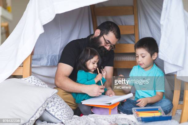 native american dad does art with his young children under a makeshift fort in the living room - fortress stock pictures, royalty-free photos & images