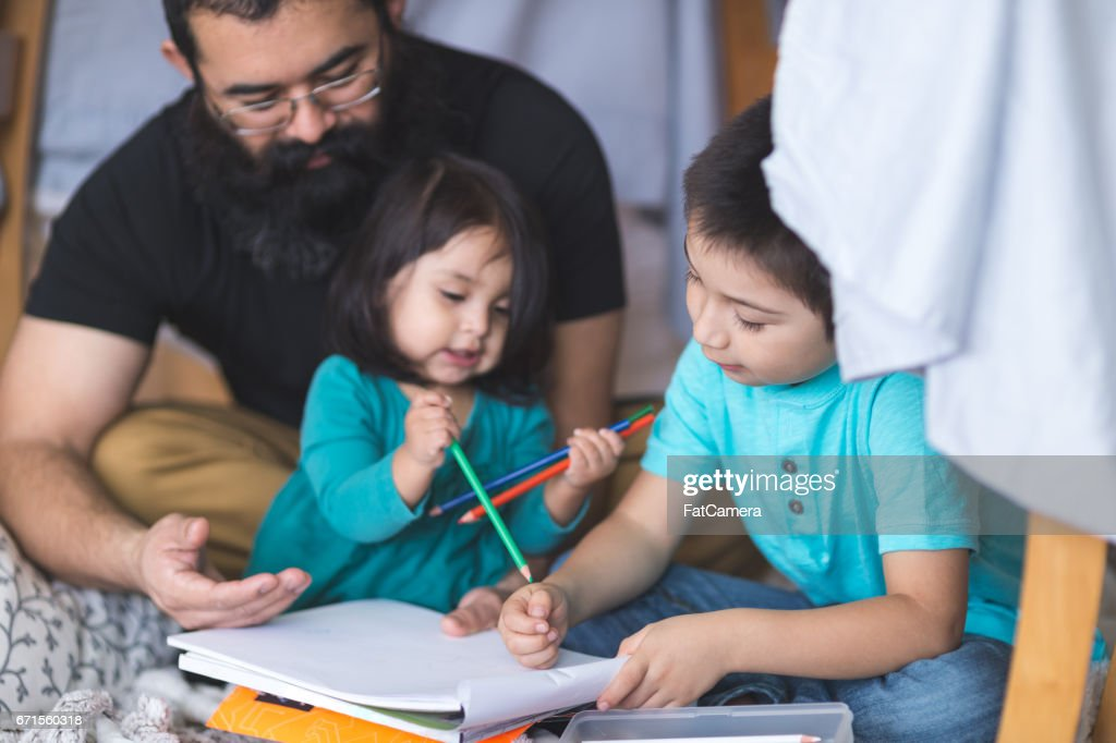 Native American dad draws with his two young children under makeshift fort in living room : Stock Photo
