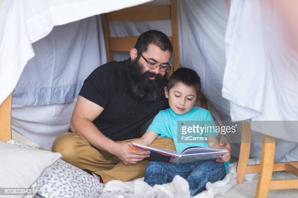 Native American dad reads with his young son under makeshift fort in living room