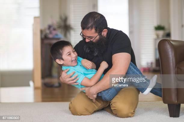 Papa d'amérindien se bat et joue avec son fils dans le salon