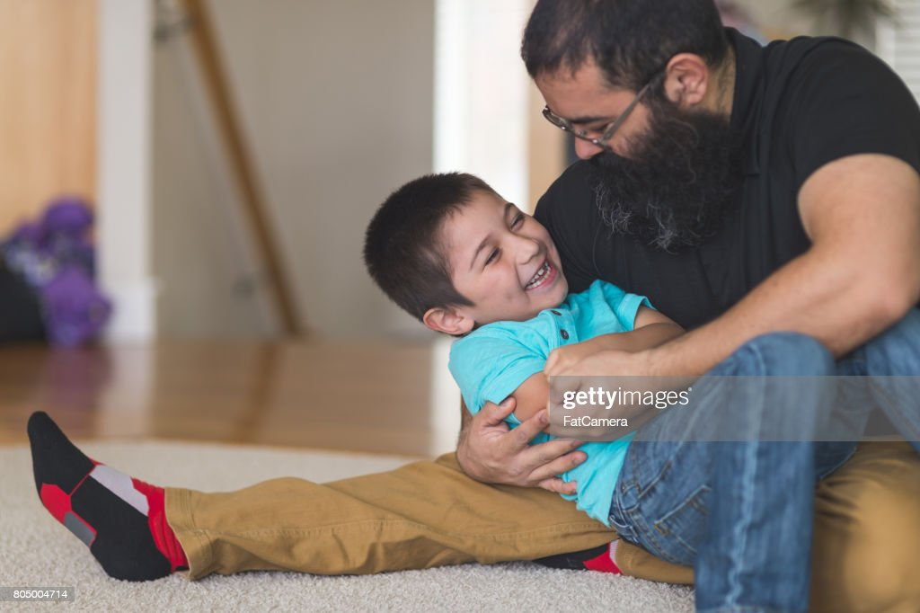 Native American dad wrestles and plays with his son in living room : Stock Photo