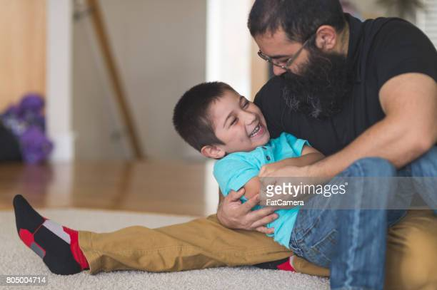 Native American dad wrestles and plays with his son in living room