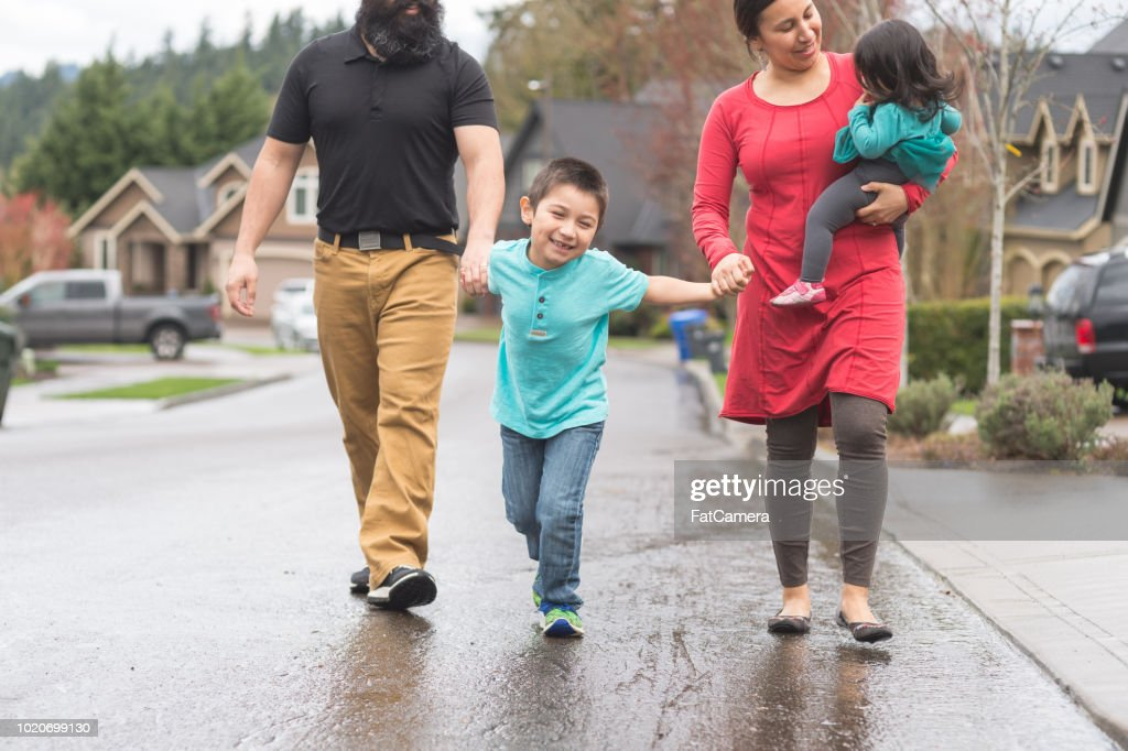 Native American family walking through a residential neighborhood together : Stock Photo
