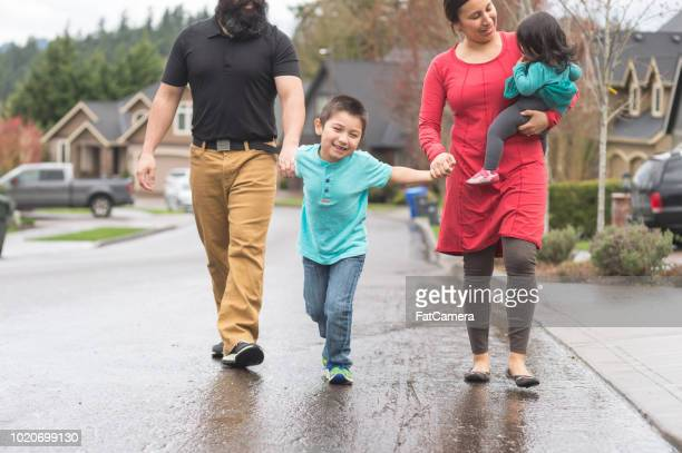 native american family walking through a residential neighborhood together - canada stock pictures, royalty-free photos & images