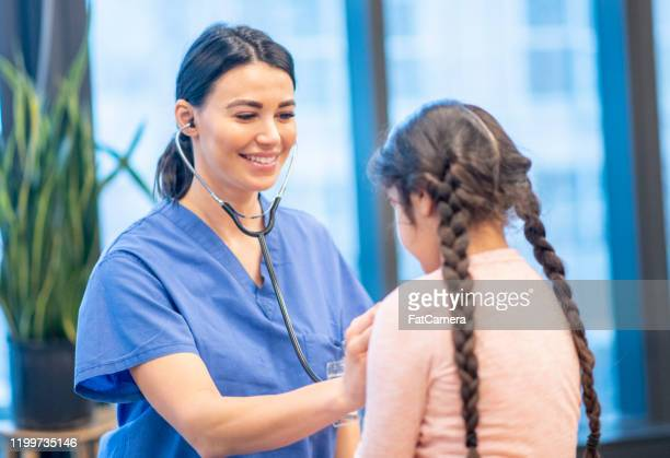 native american girl having her heart listened to stock photo - indigenous peoples of the americas stock pictures, royalty-free photos & images